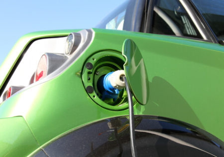 Green electric car getting charged