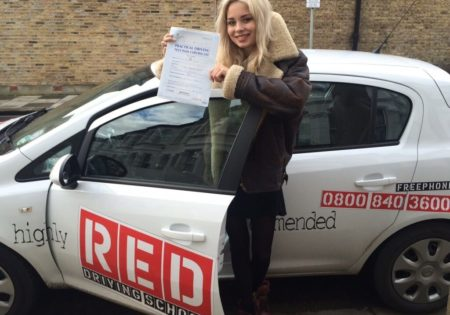 Nina Nesbitt holding driving test certificate infront of white RED car