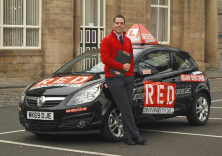 RED driving instructor leaning on RED car