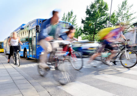 blurred cyclist infront of bus
