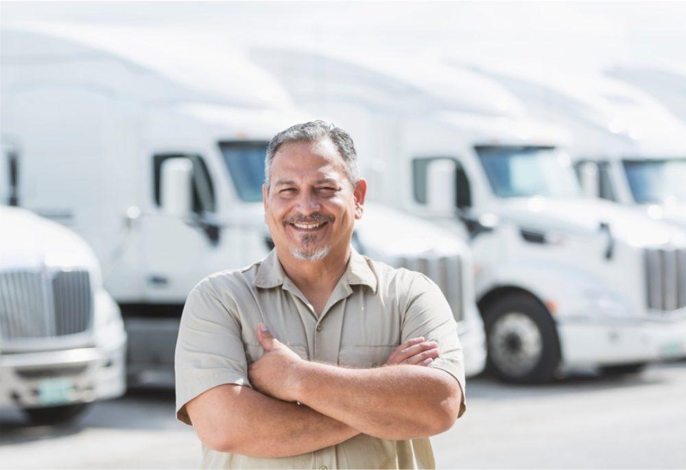 man smiling infront of white trucks