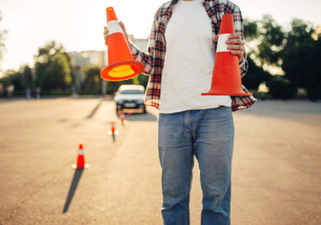 Man holding two road cones