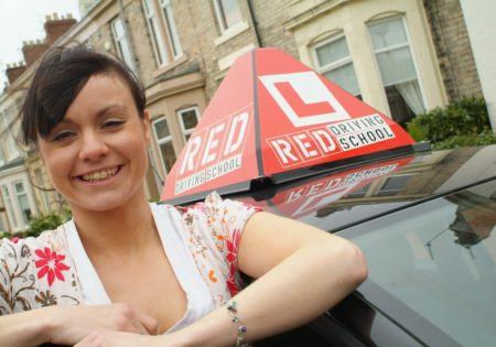 Woman and RED driving school car