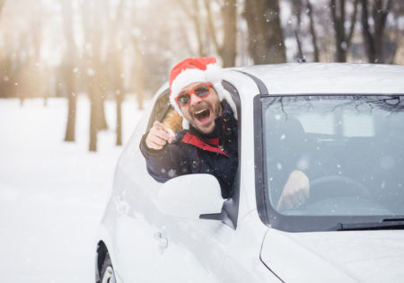 man with santa hat leaning out of car window giving thumbs up