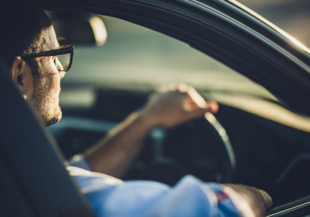 Man with glasses driving car