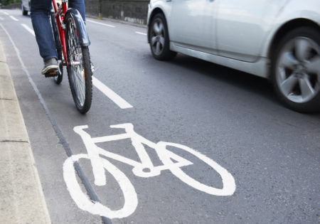 Man riding bicycle in cycle lane